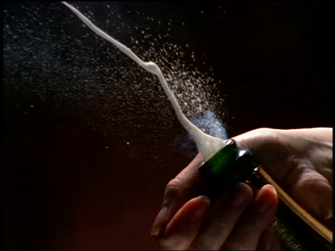 slow motion close up woman's hand popping cork from champagne bottle - bottiglia video stock e b–roll