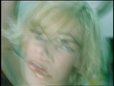 slow motion close up pan young blonde woman riding on swing in large cluttered studio looking at camera - ファンキー点の映像素材/bロール