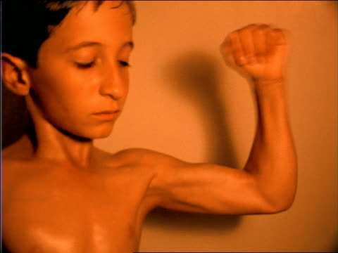 orange slow motion close up young boy flexing for camera - flexing muscles stock videos and b-roll footage