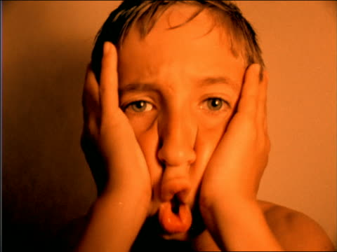 orange slow motion close up young boy making faces for camera - solo bambini maschi video stock e b–roll