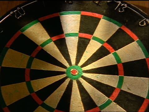 slow motion close up zoom in dart hitting bullseye on dart board - dart board stock videos & royalty-free footage