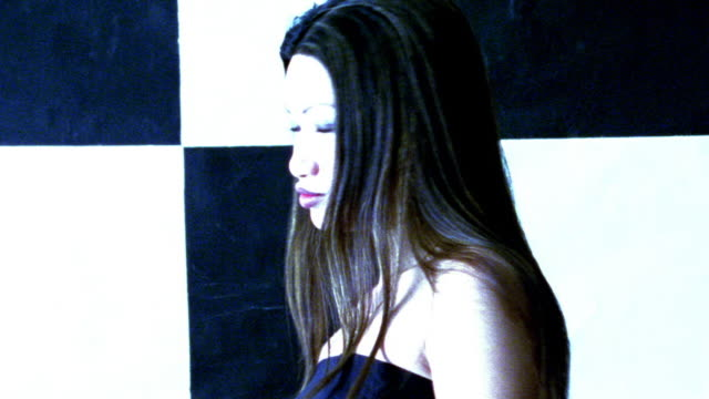 vídeos de stock, filmes e b-roll de blue high contrast slow motion close up zoom in portrait asian woman turning to camera / checkered background - superexposto