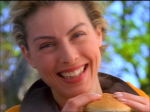 slow motion close up zoom out blonde woman smiling + laughing at camera + preparing to eat hamburger - unhealthy eating stock videos & royalty-free footage