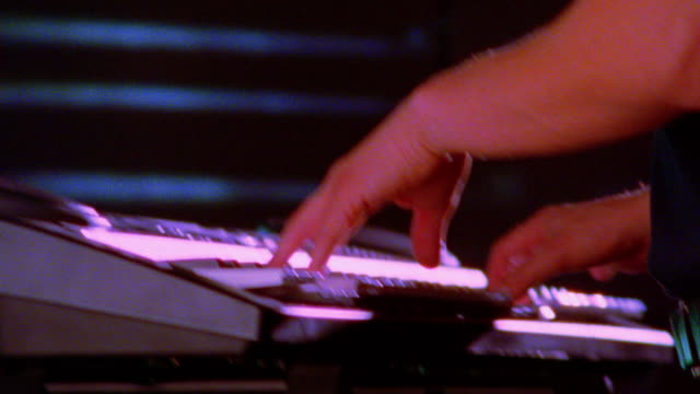 slow motion close up zoom out hands of man playing electronic keyboard /projection of close up hands playing keyboard in background