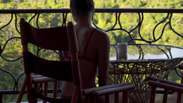 slow motion: close-up of beautiful woman in bikini sitting on balcony with cup - decor stock videos & royalty-free footage
