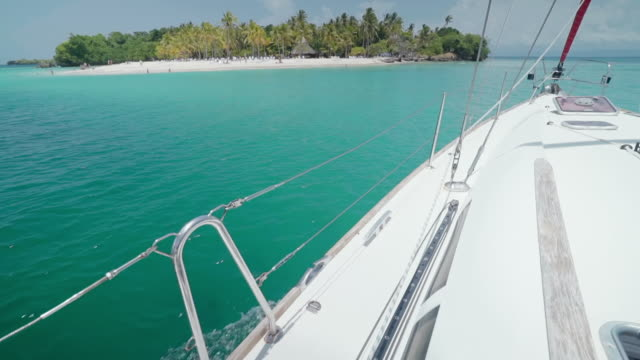 vidéos et rushes de slow motion: close-up of bow of yacht on blue ocean towards tropical island in el limon, dominican republic - voile de bateau