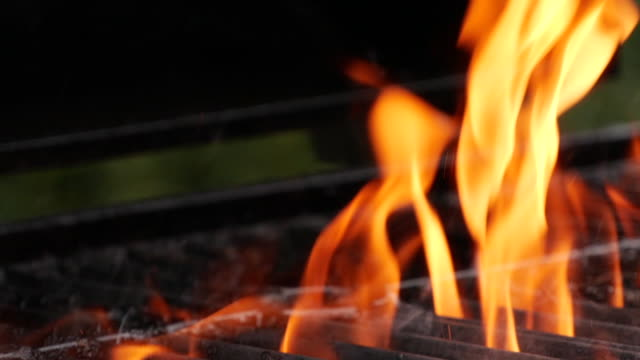 slow motion close-up of burning fire flame on grill - metal grate stock videos & royalty-free footage