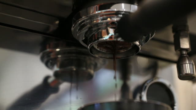 vidéos et rushes de close-up de ralenti d'espresso versant de machine à café. infusion du café professionnel - machinerie