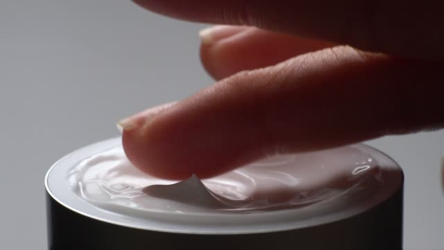 slow motion: close-up of hand touching on cream moisturizer product. - skin care stock videos & royalty-free footage
