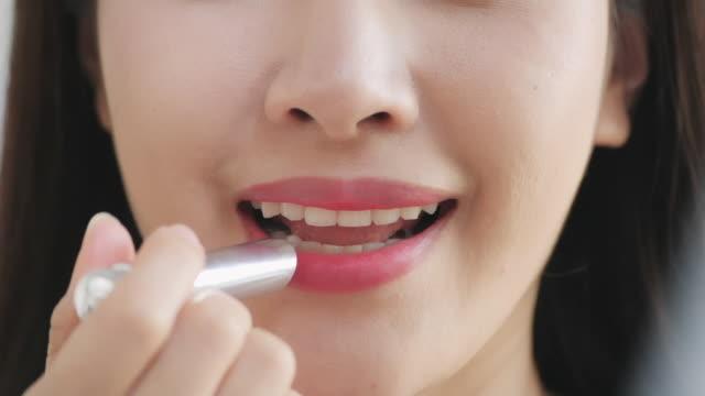 vidéos et rushes de slow motion : plan rapproché de la femme de sourire mordant ses lèvres brillantes - se mordre les lèvres