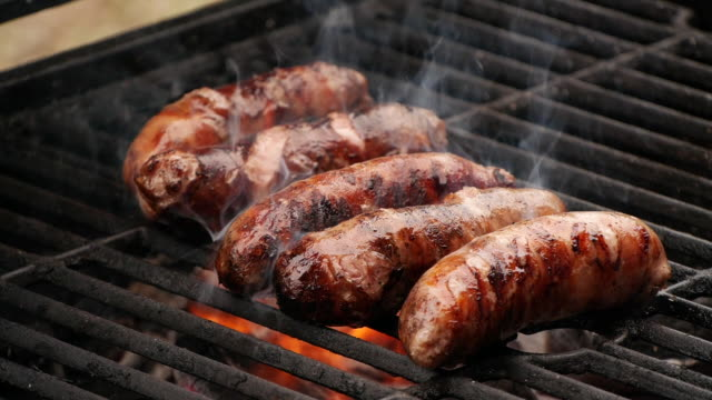 slow motion close-up sausages being cooked on grill - pollo alla brace video stock e b–roll