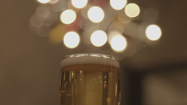slow motion close-up shot of a delicious tap beer in a glass surrounded by christmas lights blurry bokeh - beer glass stock videos & royalty-free footage