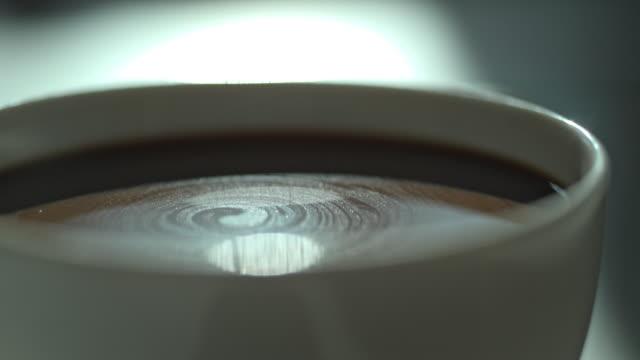 slow motion coffee cup milk creamer swirl - coffee break stock videos & royalty-free footage