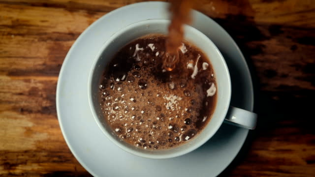 slow motion coffee pouring in cup - coffee drink stock videos & royalty-free footage