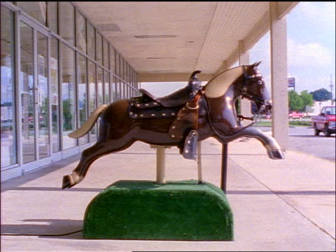 slow motion coin-operated plastic horse ride on pavement in strip mall - pflanzenfressend stock-videos und b-roll-filmmaterial
