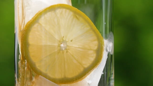 Slow motion Cola drink being poured over ice and lemon