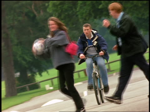 slow motion college students walking + tossing soccer ball as man rides bicycle towards camera / England