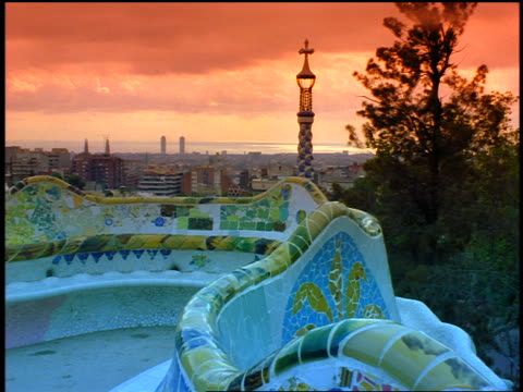 slow motion colorful mosaic bench overlooking city below / Parc Guell (Gaudi) / Barcelona, Spain