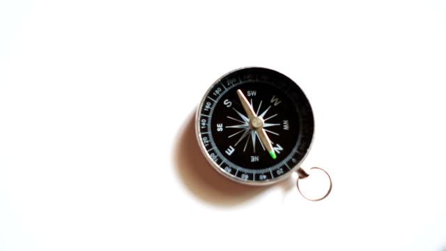 slow-motion-kompass auf weißem hintergrund - kompass stock-videos und b-roll-filmmaterial