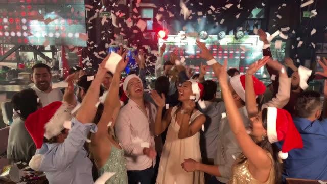 vidéos et rushes de les confettis au ralenti tombent à une fête du nouvel an dans un bar tout le monde dansant et s'amusant - party hat
