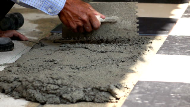 Slow Motion; Construction worker using putty knife tiling floor