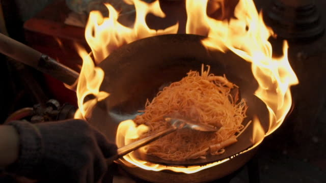 slow motion cooking food noodle with fire at street foods at night time - glove stock videos & royalty-free footage