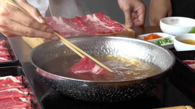 slow motion: cooking of shabu shabu suki wagyu beef meat in hot pot. - meat stock videos & royalty-free footage
