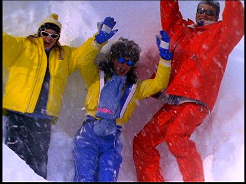 vídeos de stock e filmes b-roll de slow motion couple and young girl jumping into snowdrift - cinematografia