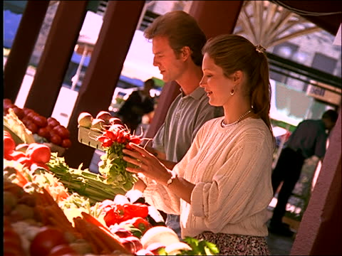 slow motion couple buying vegetables at vegetable stand - paar mittleren alters stock-videos und b-roll-filmmaterial
