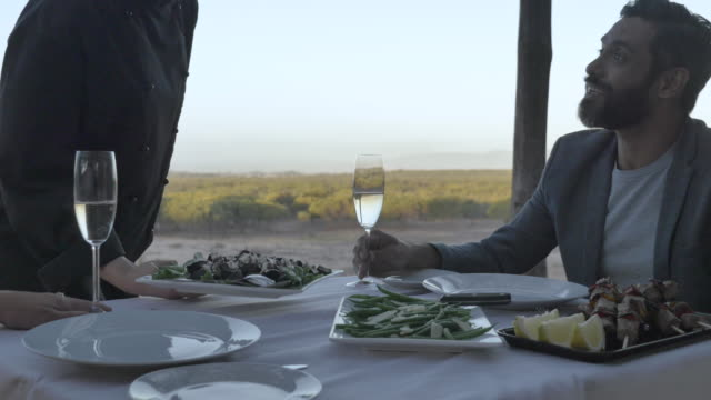 slow motion, couple eat dinner outside in south africa - waiter stock videos & royalty-free footage