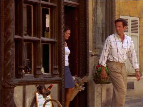 vidéos et rushes de slow motion couple exiting shop + saying goodbye to shopkeeper / france - saluer de la main
