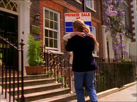 vídeos de stock, filmes e b-roll de slow motion couple hug + spin in front of house for sale / london - na frente de