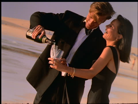 slow motion couple in formalwear pouring champagne into glasses - paar mittleren alters stock-videos und b-roll-filmmaterial