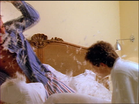 slow motion couple in pajamas having pillow fight on bed / feathers flying