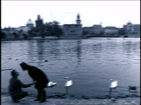 b/w slow motion pan couple kissing on banks of vltava (moldau) river near charles bridge in prague - charles bridge stock videos & royalty-free footage