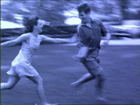 vídeos y material grabado en eventos de stock de b/w blue slow motion couple playing tag in park outdoors / nyc - imagen virada