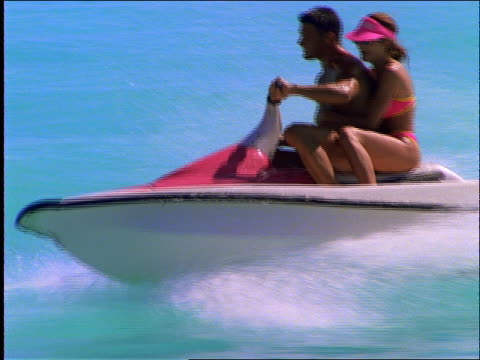 slow motion couple riding jet boat on ocean / cancun - acquascooter video stock e b–roll