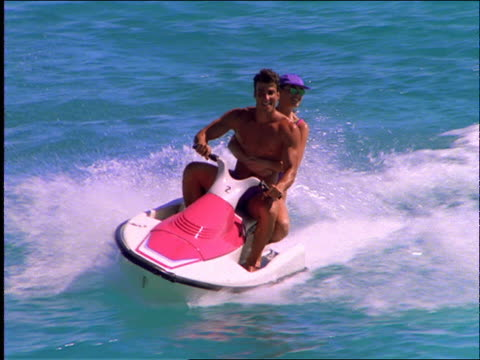 slow motion couple riding jet boat on ocean / cancun - jet ski stock videos & royalty-free footage