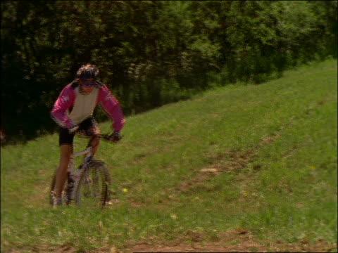 vídeos de stock e filmes b-roll de slow motion couple riding mountain bikes thru mud puddle - cinematografia