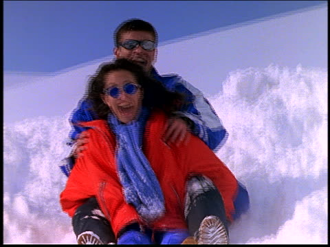 slow motion couple sledding down snowy hill / wipe out