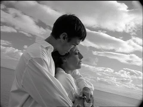 b/w slow motion couple standing on rocks by ocean cuddles - paar mittleren alters stock-videos und b-roll-filmmaterial