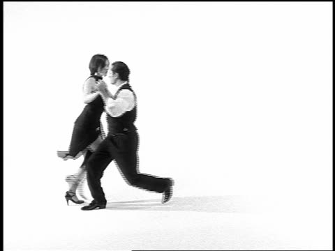 b/w overexposed slow motion couple tango dancing on white surface in studio - tango dance stock videos & royalty-free footage