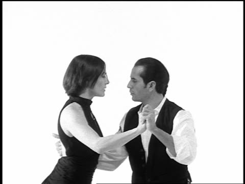 b/w overexposed slow motion couple tango dancing on white surface in studio - tangoing stock videos & royalty-free footage