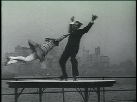 B/W 1930 slow motion couple Van Horn and Inez spinning on platform / woman holds man's tie / Governor's Island / NYC in background / July 17 1930