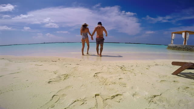 slow motion: couple walking into stunning water - one piece swimsuit stock videos & royalty-free footage