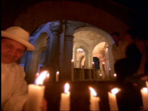 slow motion couple walking past old hispanic man kneeling by rows of candles in convent / mexico - 女子修道院点の映像素材/bロール