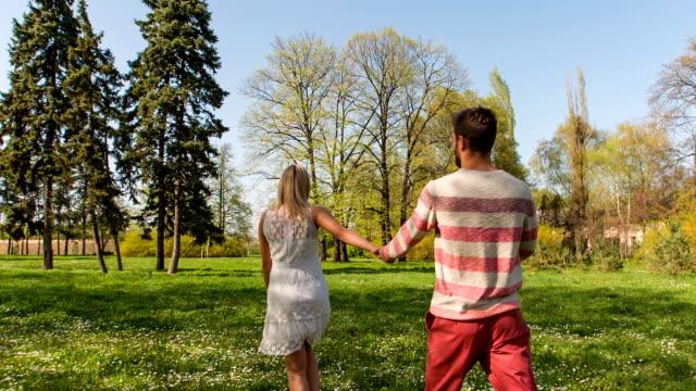 スローモーション : 歩いている夫婦から公園、手をつなぐ