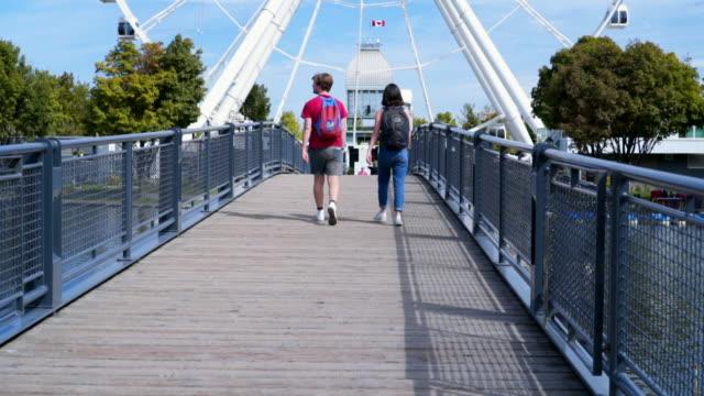 slow motion: couple walking towards montreal observation wheel - ケベック州点の映像素材/bロール