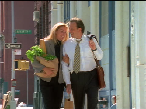 slow motion couple with groceries walking on downtown NYC street towards camera