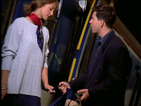 slow motion couple with luggage fighting by train then kissing / london - arguing stock videos & royalty-free footage